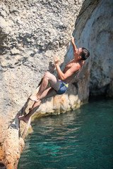 Deep water soloing, male rock climber on cliff