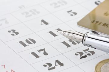 ink pen and coin money on calendar