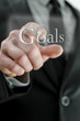 Male hand pointing at Goals icon on a touch screen interface
