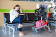 Young woman sitting with luggage hand-cart in airport lounge