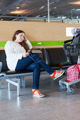 Tired female looking at tablet pc in airport lounge with luggage
