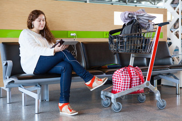 Woman looking at tablet pc in airport waiting room