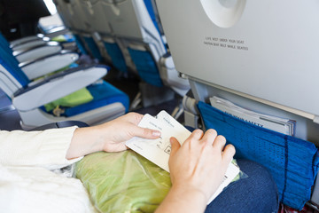 Female sitting in aircraft with boarding passes in hands
