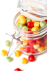 Colorful candies in glass jar. Isolated on white.