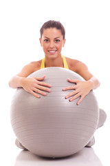 young, beautiful woman hugging big gray ball