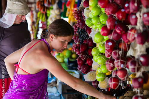 Woman chooses fruits at local market in Sri Lanka