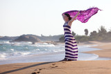 Woman stands at seashore and waves with her pareo poster
