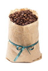 Coffee grains in a paper package with a tape on a white