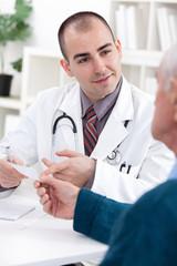 Smiling doctor giving a prescription