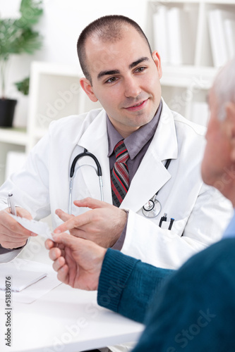 Smiling doctor giving a prescription