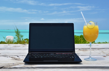 Laptop and orange juice against ocean