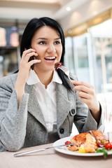 Young businesswomen eating in restaurant
