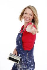 Glückliche Frau mit Pinsel und Daumen hoch - woman renovating