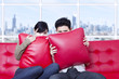 Couple hide behind pillow on red sofa