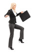 Businesswoman holding a briefcase and trying to keep balance
