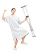 Happy male patient in hospital gown holding crutches and gesturi