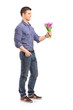 Full length portrait of a smiling guy holding flowers