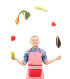 A boy with apron juggling with vegetables