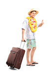 Smiling man carrying his luggage and giving thumb up