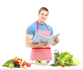 A male chef reading a cookbook while preparing a salad