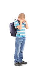 Full length portrait of a sad schoolboy crying
