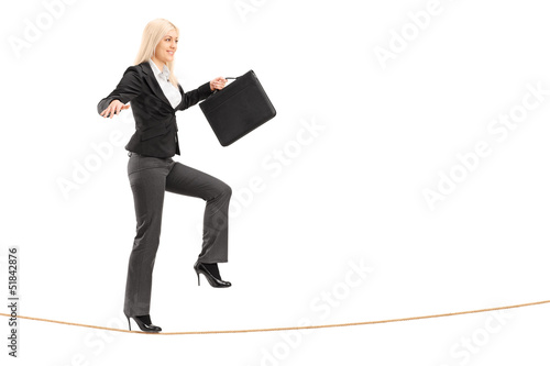 Businesswoman with briefcase, trying to keep balance while walki