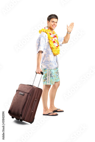 Smiling man carrying his luggage and waving goodbye