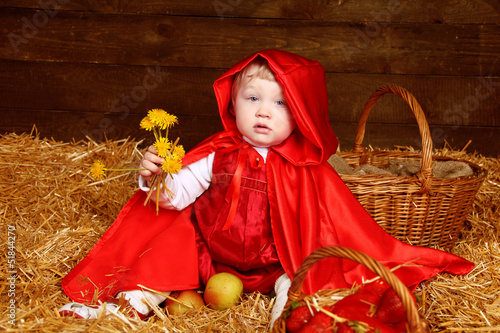 Cute little girl with dandelions wearing in red clothing resting