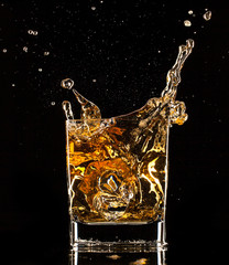 Whiskey splashing out of glass on black background