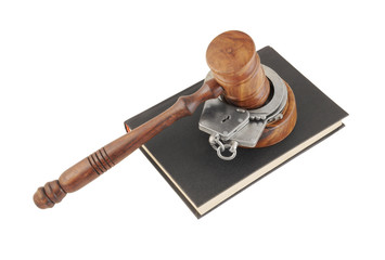 Judge's gavel and handcuffs on black legal book isolated