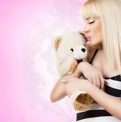 Beautiful young woman wearing pajamas embraces teddy bear