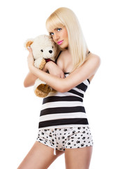 Beautiful blonde girl wearing pajamas embraces teddy bear
