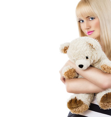Pretty blonde girl wearing pajamas embraces teddy bear on white