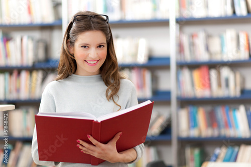 Smiling young student in a library