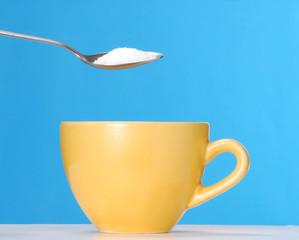 Sirviendo cucharada de azúcar en una taza de café,té.