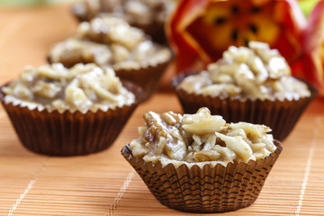 Toffee cupcakes with nuts on orange background