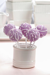 Lilac cake pops decorated lavishly decorated with icing.