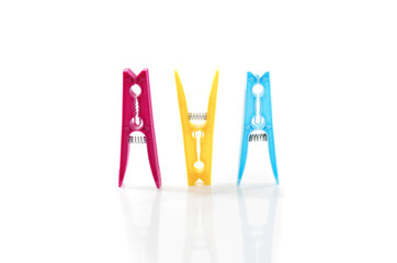 Three colored plastic clothes pegs side by side