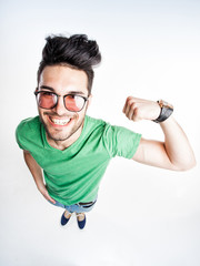 funny handsome man with hipster glasses showing muscles