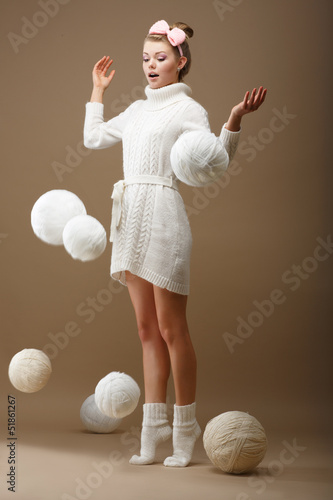 Falling Skeins. Woman in Knitted Jersey. White Balls of Yarn