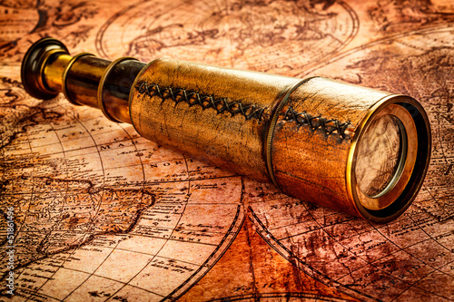Aluminium Retro Vintage spyglass lies on an ancient world map