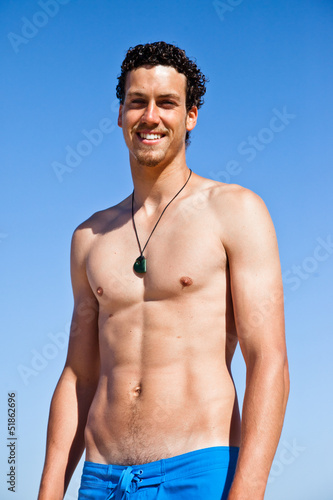 Handsome fit young man wearing a blue bathing suit