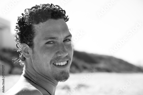 Handsome young man with a goatee smiling on the beach