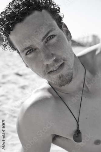 Portrait of a handsome young man with a goatee on the beach