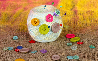 Ball of thread in the buttons on a colorful background
