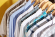 Men's shirts on hangers on yellow background