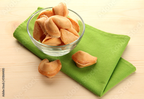 Fortune cookies in bowl, on wooden table