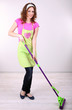 Young housewife with mop in room on grey background