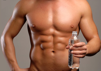 Hombre musculoso sujetando una botella de agua potable.