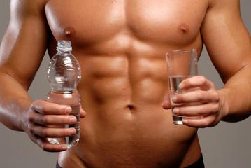 Hombre musculoso sujetando una botella y vaso de agua.